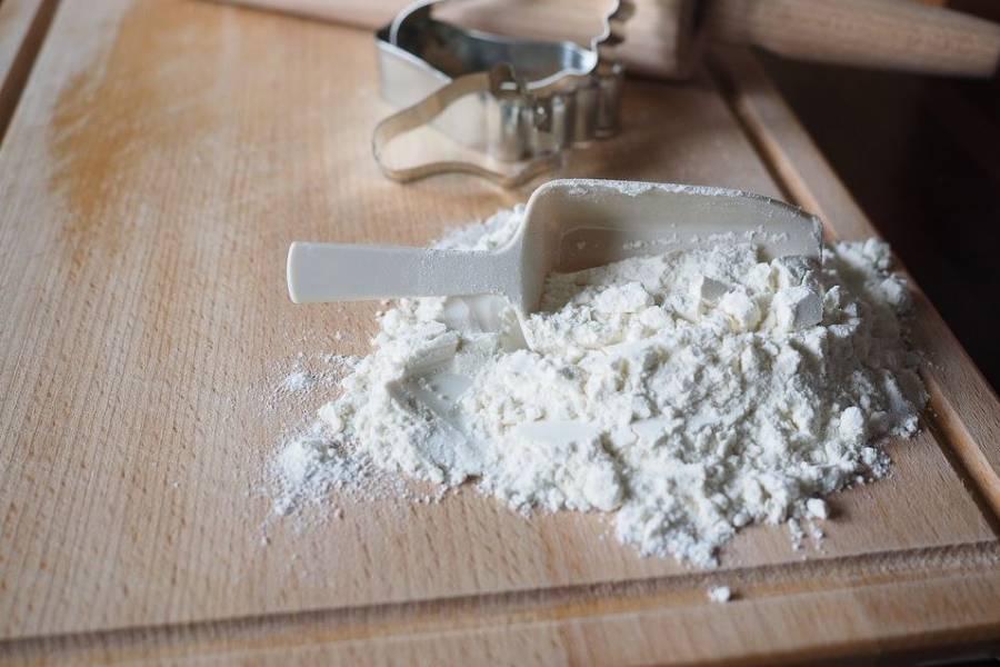 作業台の上の小麦粉とクッキー型やめん棒